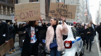 """Protesters at the Women's March on NYC, Jan. 21, 2017. Two women each hold a sign, one reading """"Take Your Tiny Hands Off My Cuntry,"""" the other, """"I am German and I've Seen This Before!!"""""""
