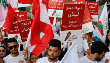 Protesters hold placards calling for the departure of Syrian refugees in Zouk Mosbeh, October 14, 2017. Arabic on the placards reads, 'So that we don't lose Lebanon. So that we don't lose our job.'