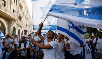 People wave Israeli flags as they take part in a parade marking Jerusalem Day, in Jerusalem May 28, 2014.
