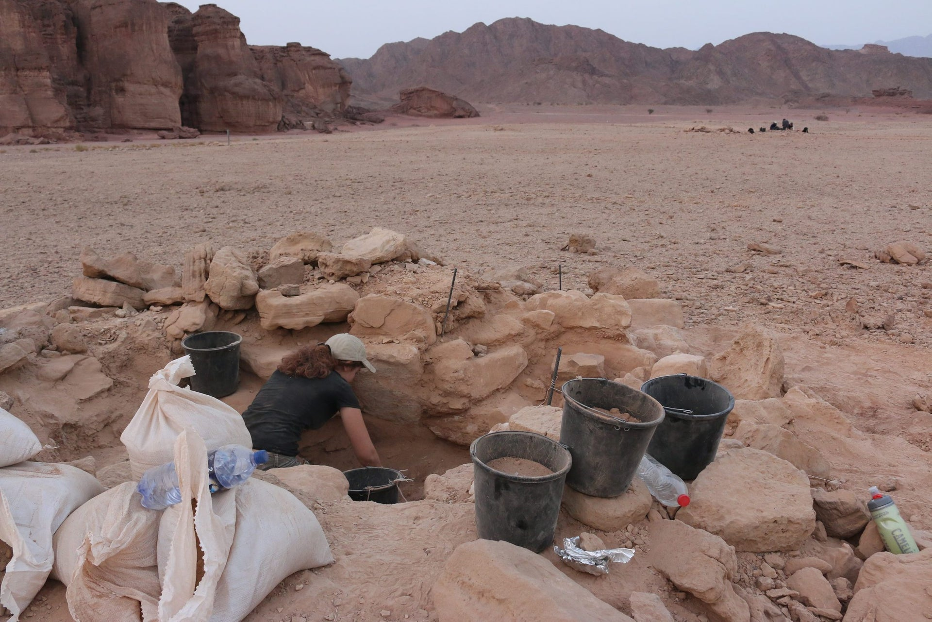 """An archaeologist excavates the """"tumulus"""" - or burial mound - that contained the woman's skeleton. Hathor's temple and the sandstone formation known as """"Solomon's Pillars"""" are on the left."""