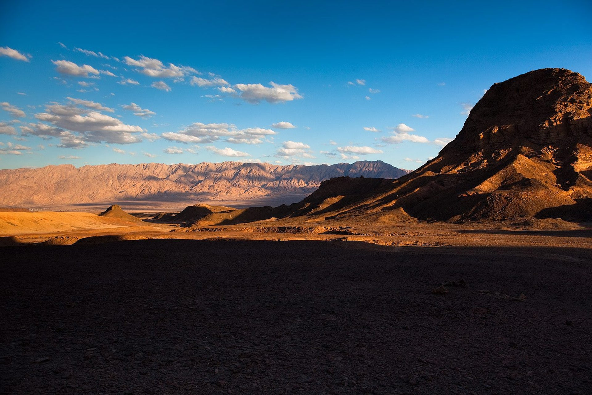 Late afternoon in Timna Valley. Photo shows stark, waterless desert landscape at Timna: A mountain looms to the right and more hills appear in the background.