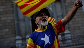 A Catalonia independence supporter wearing the Estelada flag stamped on his t-shirt claims against the Spanish State ahead the Catalan government's Generalitat building in Barcelona, Spain, Monday Oct. 30, 2017.  Spain's state prosecutor said Monday that he would seek charges of rebellion, sedition and embezzlement against members of Catalonia's ousted secessionist government, pushing the crisis over the region's independence declaration into an uncertain new phase. (AP Photo/Gonzalo Arroyo)