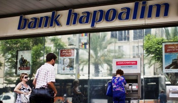 A woman uses an automated teller machine (ATM) outside a Bank Hapoalim branch in Tel Aviv, Israel May 30, 2013.