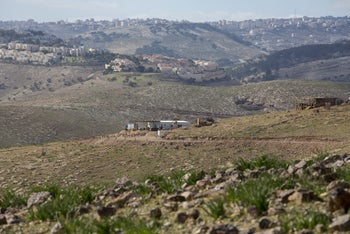Hill 387, the unauthorized West Bank settlement outpost where Jewish Shepherd operates a rehab program for teenage dropouts, in Jan. 2017. The photograph shows a few rudimentary buildings in a rocky area near a larger community.