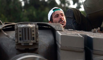 An Israeli soldier smokes a cigarette on his tank in northern Israel, August 11 2006.