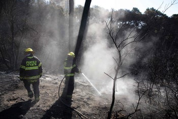 Israeli firefighters extinguish a fire in the northern Israeli city of Haifa following a wildfire, on November 25, 2016.