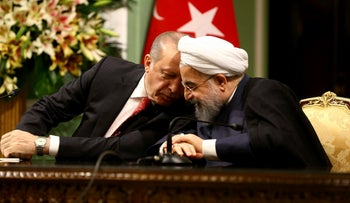 Turkish President Recep Tayyip Erdogan, left, speaks with Iranian President Hassan Rouhani during a joint press conference after their meeting at the Saadabad Palace in Tehran, Iran, Wednesday, Oct. 4, 2017.
