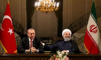 Iran's President Hassan Rouhani, right, laughs during a joint press conference with Turkey's President Recep Tayyip Erdogan following their meeting at the Saadabad Palace in Tehran, Iran, Wednesday, Oct. 4, 2017