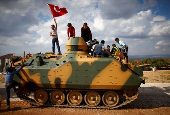 Boys stand on top of a Turkish army vehicle as a military convoy passes by their village on the Turkish-Syrian border line in Reyhanli, Hatay province, Turkey October 11, 2017.