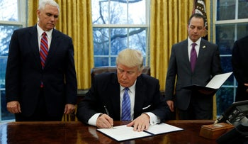 U.S. President Donald Trump signs an executive order to withdraw from the Trans-Pacific Partnership, flanked by Mike Pence (L) and Reince Priebus, January 23, 2017.