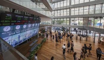 Visitors stand in front of a stock market ticker screen in the lobby of the Tel Aviv Stock Exchange in Tel Aviv, Israel, August 4, 2016.