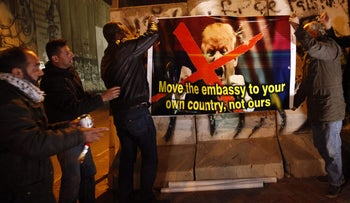 Palestinians hold a poster showing President Donald Trump during a protest in the west bank city of Bethlehem on Friday, Jan. 20, 2017.
