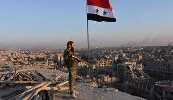 Syrian pro-government forces stand on top of a building overlooking Aleppo in the city's Bustan al-Basha neighborhood on November 28, 2016, during their assault to retake the entire northern city from rebel fighters.