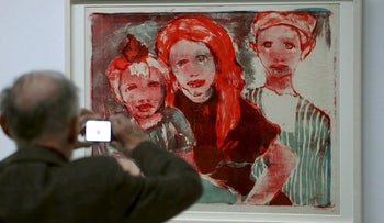 """Man takes a picture of the lithography """"Fischerkinder"""" from 1926 by late German artist Emil Nolde during a media preview of the exhibition """"Dossier Gurlitt: Degenerated Art confiscated and sold"""" at the Kunstmuseum in Bern, Switzerland November 1, 2017"""