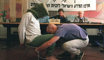 An Israeli actor demonstrating one of several standard torture techniques reportedly used by the Shin Bet security service during interrogations of Palestinian prisoners, May 19, 1998.