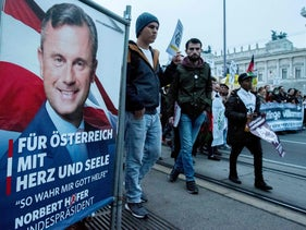 """Austrian citizens and asylum seekers march past a poster featuring presidential candidate Norbert Hofer, during a pro-refugee protest called """"Let them stay"""" in Vienna, Austria on November 26, 2016."""