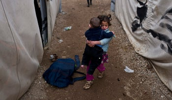 A Syrian refugee girl carries her younger brother at the refugee camp of Ritsona north of Athens, January 14, 2017.