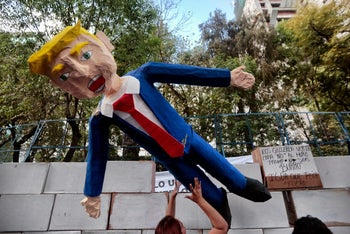 People protest against U.S. President Donald Trump's inauguration next to a fake wall with a dummy representing him in Mexico City on January 20, 2017.