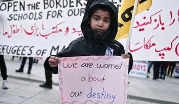 A boy carries a sign as migrants and refugees march in solidarity with the Women's March on Washington in Athens, Greece, January 21, 2017.