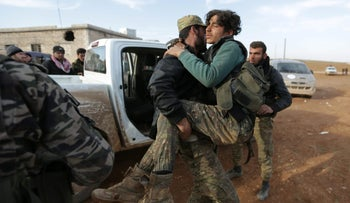 A Free Syrian Army fighter carries a fellow fighter injured during an offensive against ISIS fighters, near the northern Syrian town of al-Bab, January 12, 2017.
