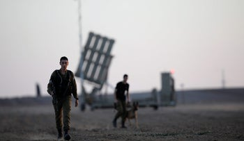 Israeli soldiers walk past an Iron Dome rocket interceptor battery deployed near central Gaza Strip, southern Israel October 31, 2017.