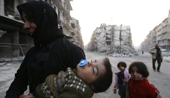 A Syrian woman and her children walk past destroyed buildings in Aleppo's formerly rebel-held al-Shaar neighborhood on January 21, 2017, after government forces retook the city.