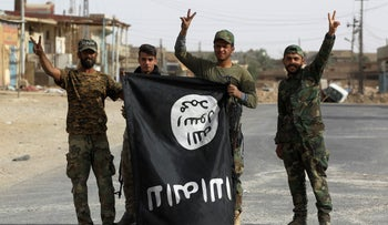 Iraqi members of the Hashed al-Shaabi victoriously carry an upside-down Islamic State (IS) group flag in the city of al-Qaim on November 3, 2017.