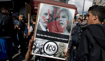 Palestinian carries a poster with a defaced photo of U.K. Prime Minister Theresa May, and Arthur Balfour, on the 100th anniversary of the Balfour Declaration, in Ramallah, Nov. 2, 2017.