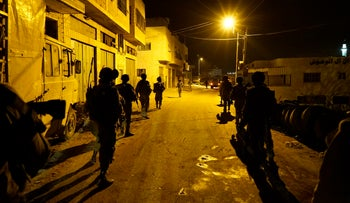 IDF troops seen patrolling the streets of a Palestinian village near the West Bank city of Hebron at night.