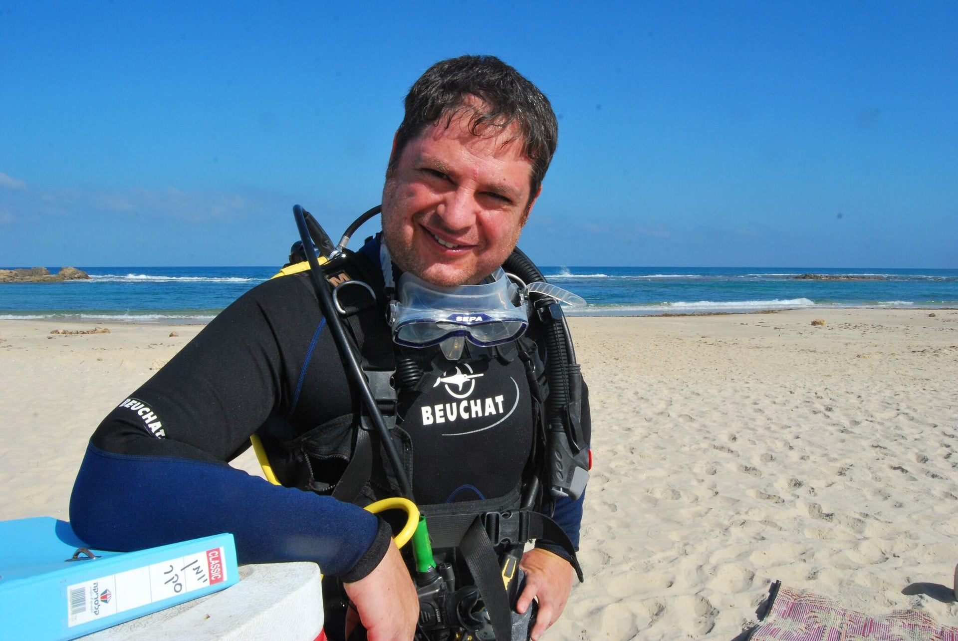 """Marine archaeologist Dr. Assaf Yasur-Landau, in diving gear: """"We knew that another storm would be coming within days, so we decided to extract it rather than risk the stone being reburied in the sand."""""""
