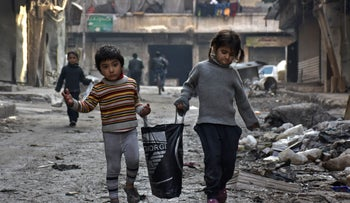 Syrian children walk carrying a bag along a damaged street in Aleppo's Tareeq al-Bab neighbourhood on January 18, 2017, a month after government forces retook the northern Syrian city from rebel fighters.