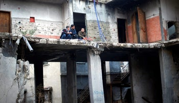Palestinians sit in a house damaged during 2014's Operation Protective Edge in Beit Hanoun, Gaza Strip, December 15, 2016.