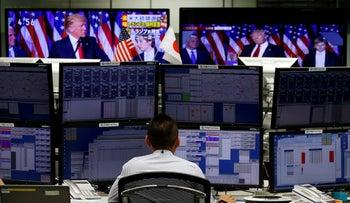 An employee of a foreign exchange trading company works near monitors showing U.S. President-elect Donald Trump, Tokyo, Japan, November 9, 2016.