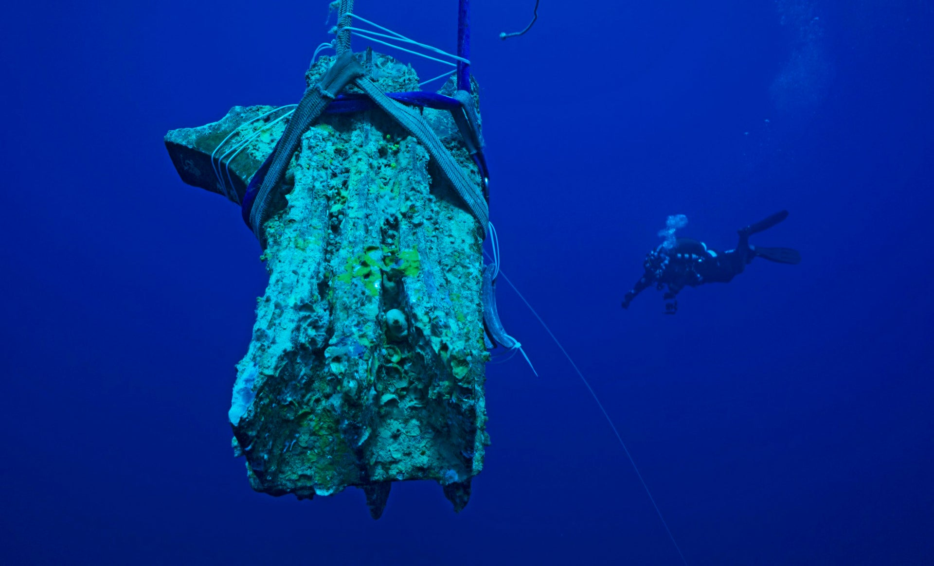 Raising a bronze ram found by diving archaeologists at Egadi, Silicy from First Punic War. The foreground shows the ram, encrusted after over 2,000 years some 120 meters under the sea, strapped and being raised. In the background of the deep blue sea, we can see a diver.