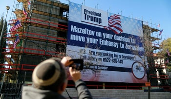 A man takes a picture of a giant banner on a building congratulating U.S. President-elect Donald Trump in Jerusalem, January 20, 2017.