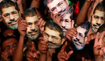 Members of the Muslim Brotherhood and supporters of deposed Egyptian President Mohamed Morsi hold up masks of him as they gather at the Rabaa Adawiya square, where they are camping, in Cairo July 12, 2013.