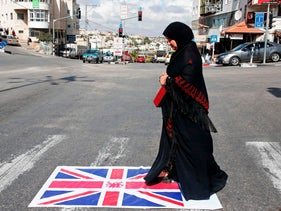 A Palestinian woman walks over a Union Jack flag in Halhul, north of the West Bank town of Hebron, as Palestinians demonstrate on the 100th anniversary of the Balfour agreement which helped lead to Israel's creation and the Israeli-Palestinian conflict on November 2, 2017. / AFP PHOTO / HAZEM BADER