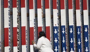A person peers through a section of a U.S.-Mexico border wall with activist graffiti displayed in Tijuana, Mexico, on Wednesday, Jan. 25, 2017.