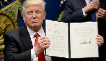 U.S. President Donald Trump holds up signed executive orders to bar refugees and travelers from seven Muslim-majority countries, January 27, 2017.