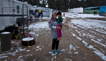 A pregnant Syrian refugee holds her daughter Zinnar, 5, by the entrance of her shelter in the refugee camp of Ritsona, Greece, December 30, 2016.