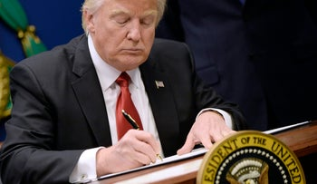 U.S. President Donald Trump signs executive orders to bar refugees and travelers from seven Muslim-majority countries, January 27, 2017.