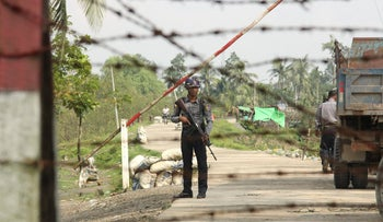 "A Myanmar police officer stands watch as journalists arrive in Shwe Zar village in the suburb of Maungdaw town, northern Rakhine state of Myanmar, on Wednesday, Sept. 6, 2017. Myanmar leader Aung San Suu Kyi's top security adviser sought to counter the storm of criticism the government is facing from around the world over alleged army abuses against ethnic minority Rohingya, asserting that security forces were acting with restraint in pursuing ""terrorists."" (AP Photo)"