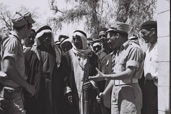 Israeli soldiers and Arab citizens stand outside the office of the military administration, Be'er Sheva, Israel, 1950.