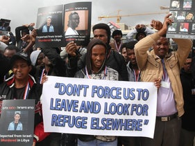 Eritrean asylum seekers, who entered Israel illegally during the past years, hold placards showing their compatriots who they say were killed after being deported to Eritrea, during a protest against Israel's deportation policy in front of the Supreme Court in Jerusalem on January 26, 2017.