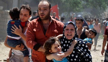 A Palestinian woman runs carrying a girl following what police said was an Israeli air strike on a house in Gaza city July 9, 2014.