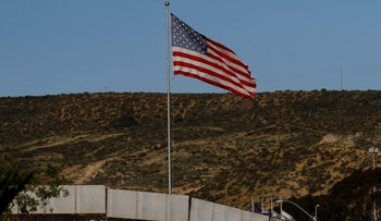 A U.S. flag is seen next to a section of the wall separating Mexico and the United States, in Tijuana, Mexico, January 28, 2017.