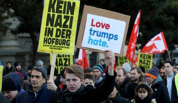 Protesters walk during a demonstration against Norbert Hofer, candidate for presidential elections of Austria's right-wing Freedom Party, FPOE, in Vienna, Austria, Saturday, Dec. 3, 2016. The poster on the left reads 'No Nazis in the Hofburg' referring to Austria's presidential palace.