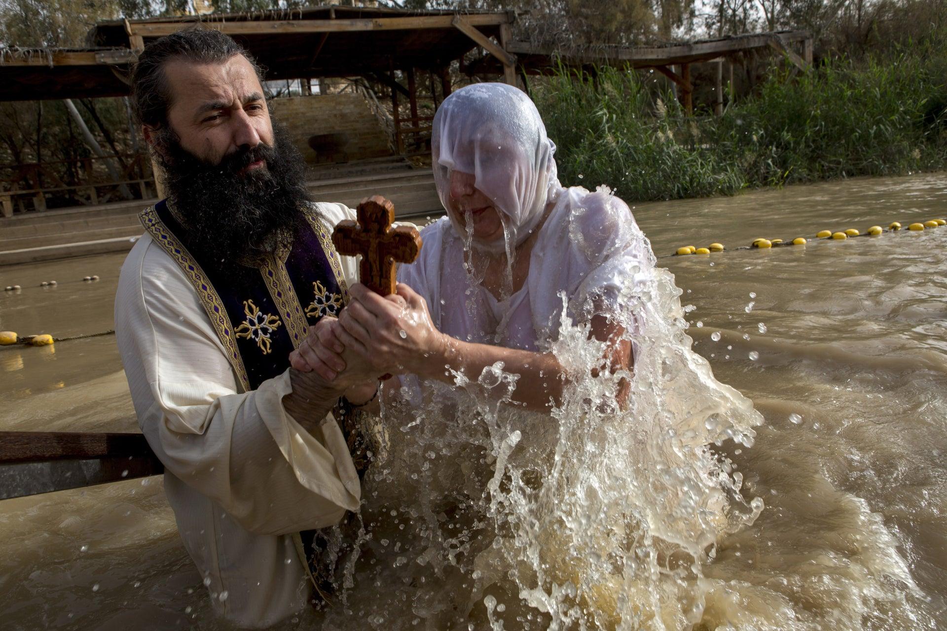 A Christian pilgrim prays as she dips in the water at the baptismal site known as Qasr el-Yahud on the banks of the Jordan River near the West Bank city of Jericho.