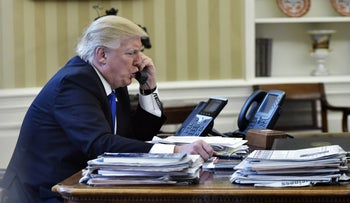 U.S. President Donald Trump speaks on the phone with Germany's Chancellor Angela Merkel from the Oval Office of the White House on January 28, 2017.