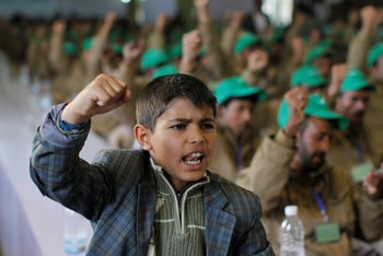 A boy shouts slogans next to pro-Houthi fighters injured during recent fighting, during a rally in Sanaa, Yemen, on January 29, 2017.